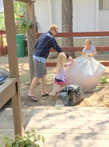 Nick, Abby and Savannah move pine needles to the big pile.