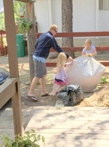 Nick, Abby and Savannah move pine needles to the big pile.